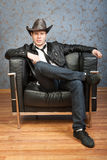 Young cowboy sitting in leather chair. Young cowboy sitting in a chair against a background of patterned walls Stock Photography
