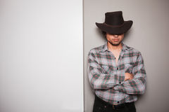 Young cowboy standing against dual colored background. A young cowboy is standing a against a green and white background Stock Image