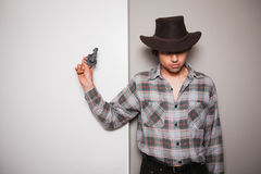 Young cowboy standing against dual colored background. A young cowboy is standing a against a green and white background Stock Photography