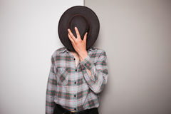 Young cowboy standing against dual colored background Stock Images