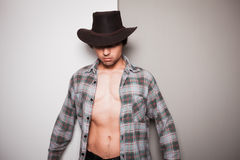 Young cowboy standing against dual colored background. A young cowboy is standing a against a green and white background Royalty Free Stock Image