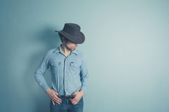 Young cowboy is standing by a blue wall. A young cowboy dressed in denim is standing by a blue wall Royalty Free Stock Photography