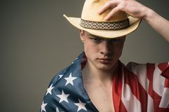 Young cowboy in straw hat wrapped in USA flag isolated on gray background. American dream, Independence Day celebration. July 4 Stock Photos