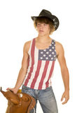 Young cowboy in striped shirt saddle in hand Stock Photography