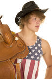 Young cowboy in striped shirt saddle on shoulder. A young cowboy holding on to his saddle on his shoulder looking to the side Royalty Free Stock Photography