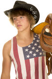 Young cowboy in striped shirt on shoulder look to side. A young cowboy looking to the side, holding on to his saddle Royalty Free Stock Photo