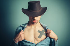 Young cowboy unbuttoning his shirt Stock Images