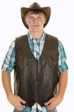 Young cowboy in vest looking. A young cowboy with a western vest on looking forward royalty free stock photo