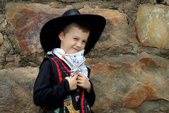 Young cowboy winking at camera. Smiling under hat and holding onto his toy guns Stock Images