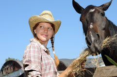 Young cowgirl feeding horse Royalty Free Stock Images