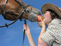 Young cowgirl and her friend eating an apple Royalty Free Stock Images