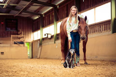 Young Cowgirl With Her Horse And Dog. In indoors riding arena Royalty Free Stock Image