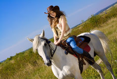 Young cowgirl on horse. Young cowgirl on white horse Royalty Free Stock Photo