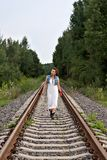 Young  cowgirl in old-fashioned clothes walking on rails Stock Photography