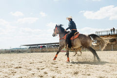 Young cowgirl riding a beautiful paint horse in a barrel racing event at a rodeo. Royalty Free Stock Image