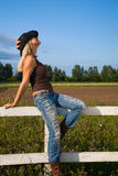 Young cowgirl sitting on a fence Royalty Free Stock Photos