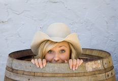 Young cowgirl smiling from inside a barrel. A beautiful young cowgirl hides in a barrel, smiling, seeming surprised Royalty Free Stock Photos