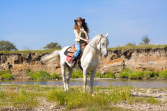 Young cowgirl on white horse at the river. Blue sky Stock Photography
