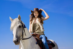Young cowgirl on white horse smile. Blue sky Royalty Free Stock Images
