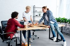 Young coworkers eating pizza together while working together. In office stock photo