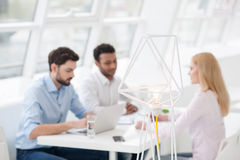 Young coworkers having brainstorming session in modern offic. Creative lighting. Close up of creative floor lamp in modern office with team of staff in Royalty Free Stock Image