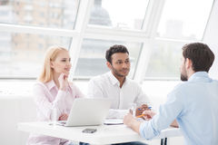 Young coworkers having brainstorming session in modern office. They are coming up with another great idea. Group of cheerful business people sitting together at Royalty Free Stock Image