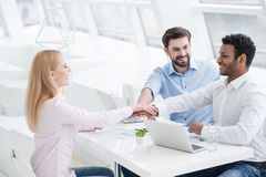 Young coworkers having brainstorming session in modern office. Creative planning in progress. Friendly group of staff putting their hands together Royalty Free Stock Photos