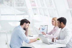 Young coworkers having brainstorming session in modern office. Ddiscussing new challenge. Young smiling businesswoman discussing something with colleagues Stock Photo