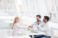 Young coworkers having brainstorming session in modern office. Everyday winners. Group of happy business people looking at each other and gesturing Royalty Free Stock Photo
