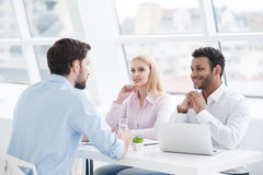 Young coworkers having brainstorming session in modern office. Sharing ideas with a smile. Casual business team having meeting in creative office Stock Images