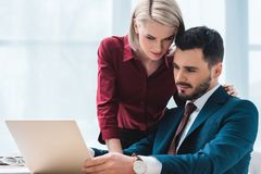 young coworkers using laptop and flirting stock images