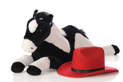 A Young Cowpoke's Horse. A child's bright red cowboy hat by a large plush horse. Isolated on white stock image