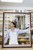 Young craftsman looking on frame's corner in workshop Royalty Free Stock Photography