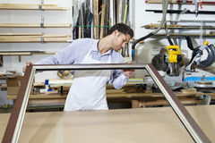 Young craftsman looking at picture frame Royalty Free Stock Photo