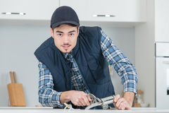 Young craftsman repairing tap in kitchen Royalty Free Stock Photography