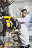 Young craftsman wearing protective gear while using circular saw Stock Image