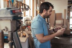 Young craftsmen using a tablet in his woodworking workshop Stock Image
