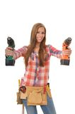 Young craftswoman with two driller. Young artisan with a tool belt shows two drill Stock Photos