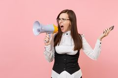 Young crazy angry business woman in black suit, glasses screaming holding megaphone and mobile phone on pink. Background. Lady boss. Achievement career wealth royalty free stock photos