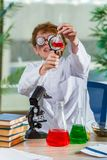 The young crazy chemist working in the lab Royalty Free Stock Photography