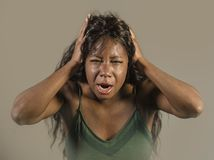 Young crazy desperate and anxious black african American woman feeling stressed and tormented in intense and dramatic face express. Ion isolated on studio stock image
