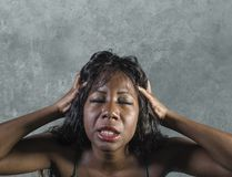 Young crazy desperate and anxious black african American woman feeling stressed and tormented in intense and dramatic face express. Ion isolated on studio stock images