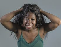 Young crazy desperate and anxious black african American woman feeling stressed and tormented in intense and dramatic face express. Ion isolated on studio royalty free stock photo