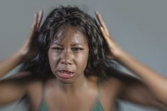 Young crazy desperate and anxious black african American woman feeling stressed and unwell in intense and dramatic face expression. Isolated on studio stock photography