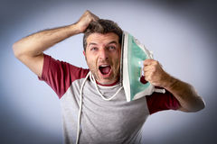 Young crazy desperate and frustrated man doing housework holding iron Royalty Free Stock Images