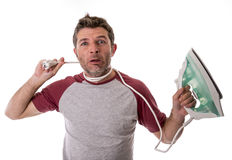 Young crazy desperate and frustrated man doing housework holding Stock Photo