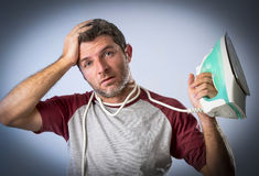 Young crazy desperate and frustrated man doing housework holding iron Stock Images