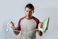 Young crazy desperate and frustrated man doing housework holding iron Royalty Free Stock Photos