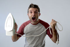 Young crazy desperate and frustrated man doing housework holding iron Stock Photo