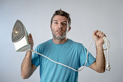Young crazy desperate and frustrated man doing housework holding Royalty Free Stock Photo